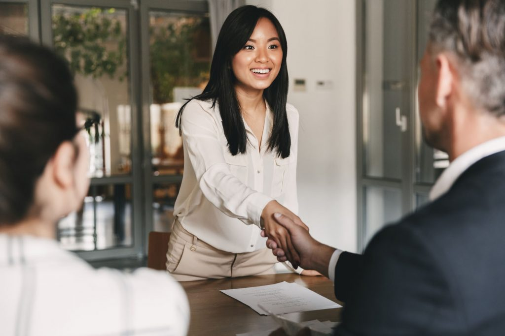 Young woman shaking hands with her boss
