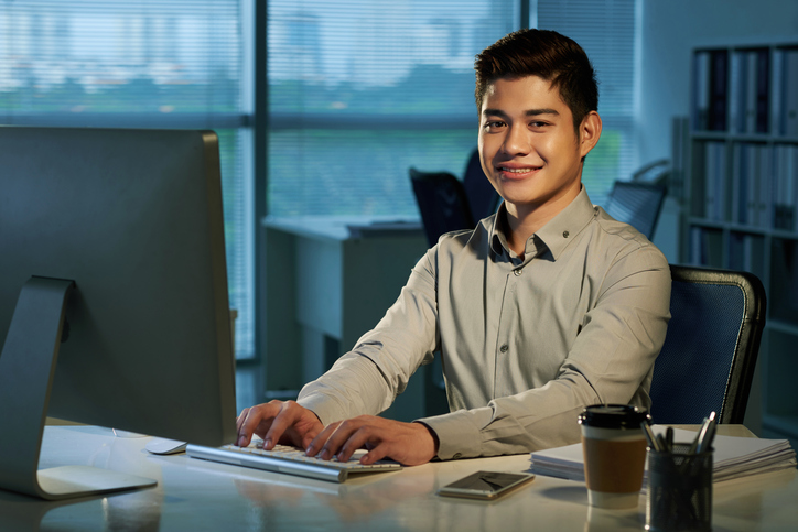 Filipino man smiling and working on a computer