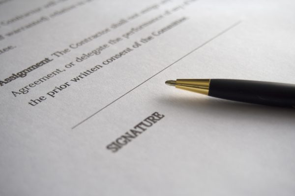 An open pen on a contract over the signature line